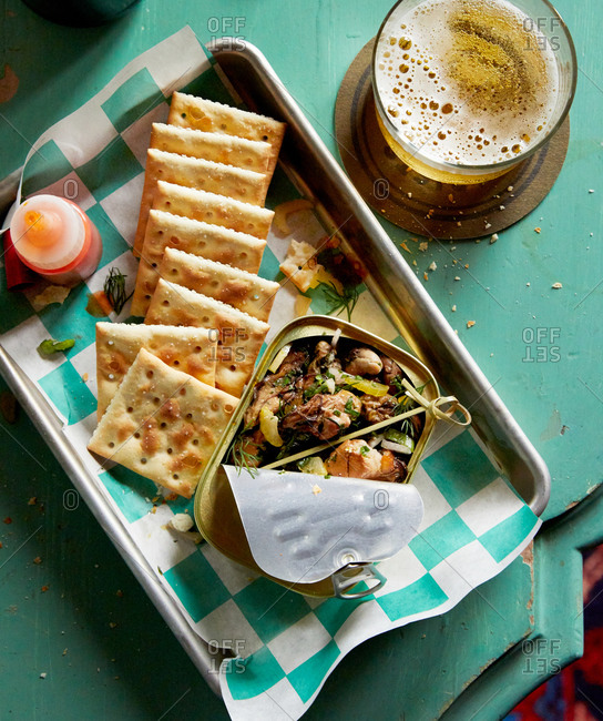 Overhead view of saltine crackers and sardines served with beer