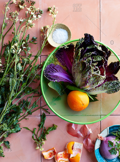 Orange and purple lettuce in a strainer beside flowers
