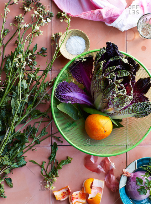 Orange and purple lettuce in a strainer beside flowers on pink tile background