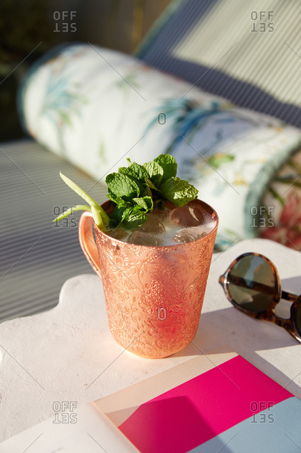 Moscow mule cocktail beside an outdoor poolside lounge chair