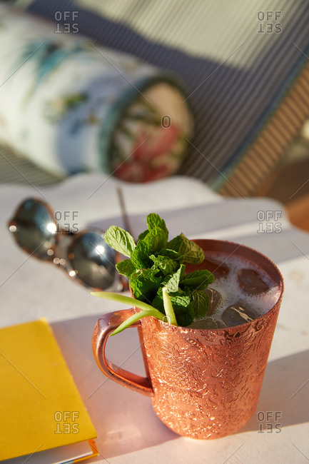 Close up of a Moscow mule cocktail beside an outdoor poolside lounge chair
