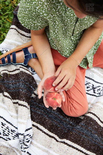 Overhead view of child holding Saturn peaches
