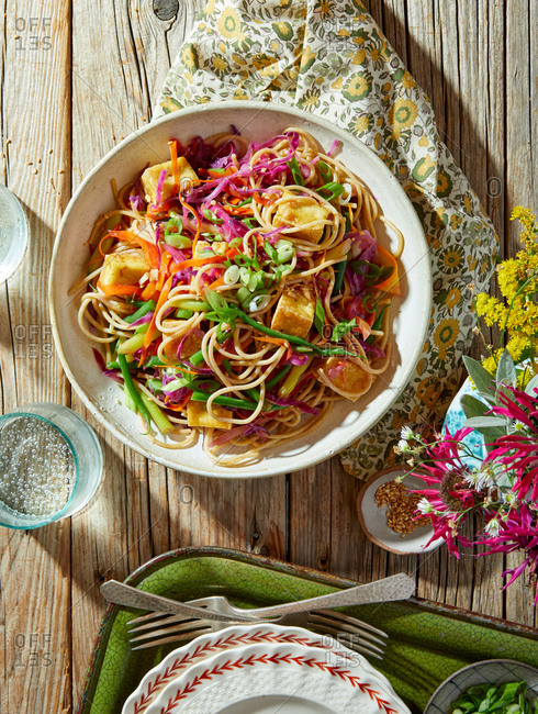 Overhead view of a colorful tofu pasta dish on a rustic wooden table