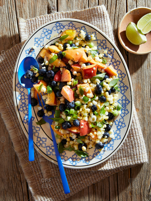 Overhead view of a corn, apple and blueberry salad on a rustic wooden table