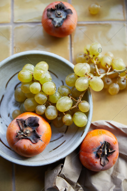 Persimmons and grapes on tile background