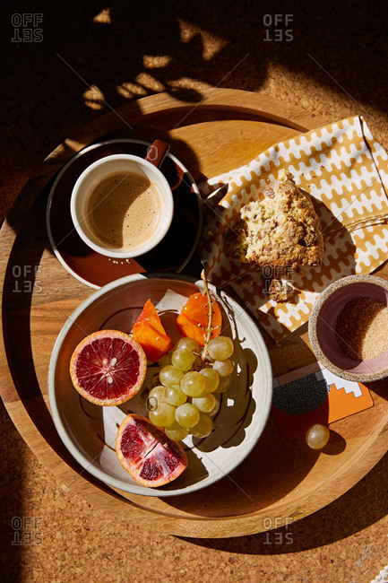 Pastry served with coffee and fruit on wooden tray