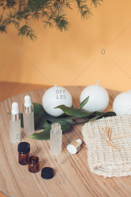 Essential oils and round candles on wooden tray with towel