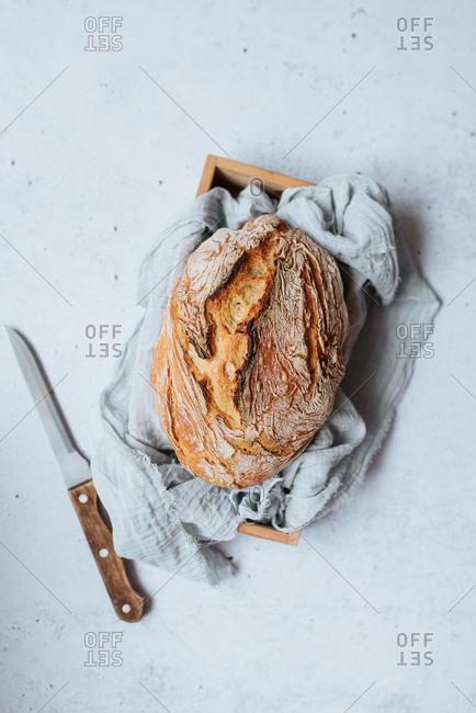 Overhead view of homemade artisan bread on light surface beside knife
