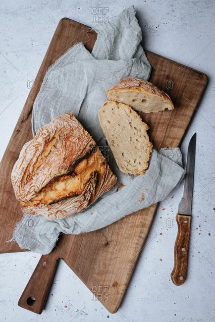 Homemade artisan bread sliced on a cutting board beside knife