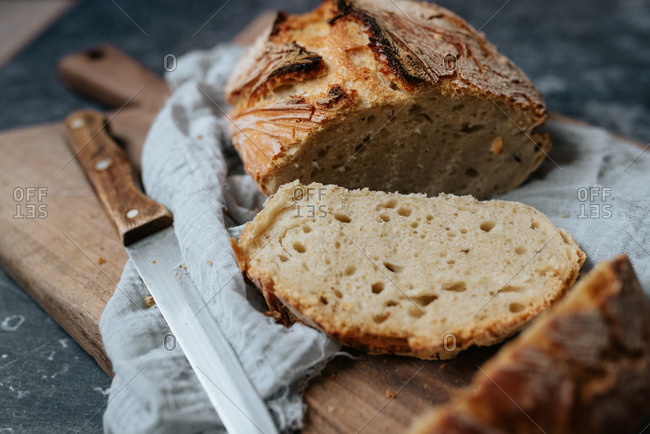 Close up of homemade artisan bread sliced on a cutting board with a knife