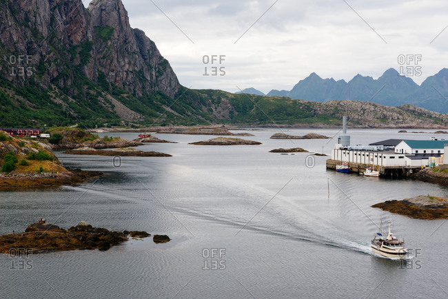 Picturesque landscape of sea bay surrounded by majestic rocky mountains with small buildings on shore and ship floating on water under cloudy sky