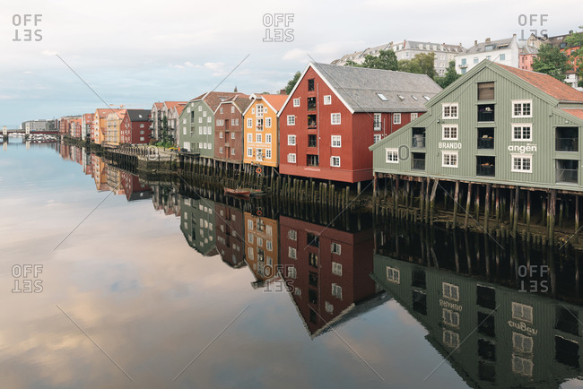 March 30, 2020: Peaceful scenery with colorful small houses built in row on shore of lake and reflected in calm water under blue cloudy sky