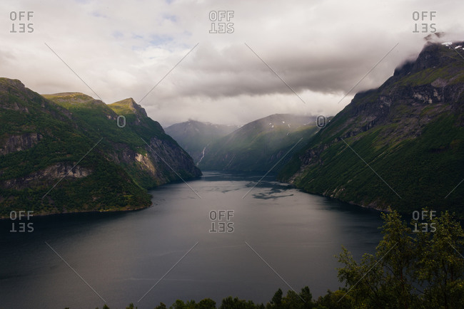 From above landscape of fjord with majestic rocky cliffs covered with green grass on sides under cloudy sky