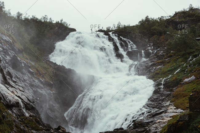 Natural landscape of raging river with powerful waterfall cascade with foam streaming in rough rocky terrain