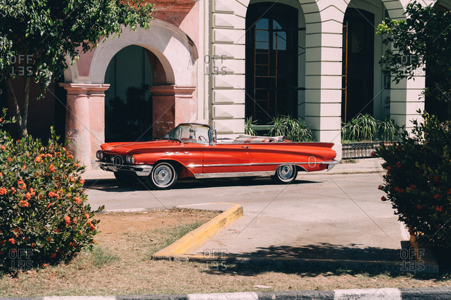 March 30, 2020: Red retro open top automobile parked near entrance of old colonial stone building with arches and columns in sunny day in Havana