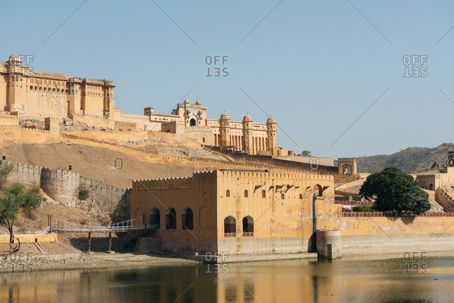Old stone palace with beautiful architecture located near lake in ancient city of India under clear blue sky