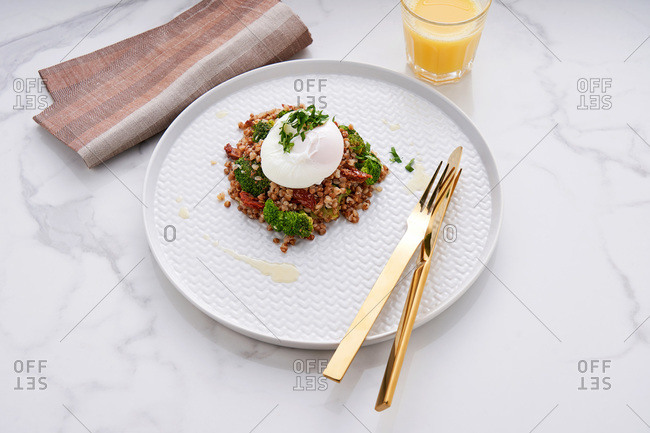 Healthy and gluten free breakfast of buckwheat with broccoli and sun-dried tomatoes topped with a poached egg