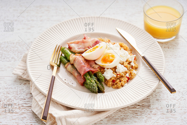 Spelt with bacon, asparagus, feta and egg on white wood background