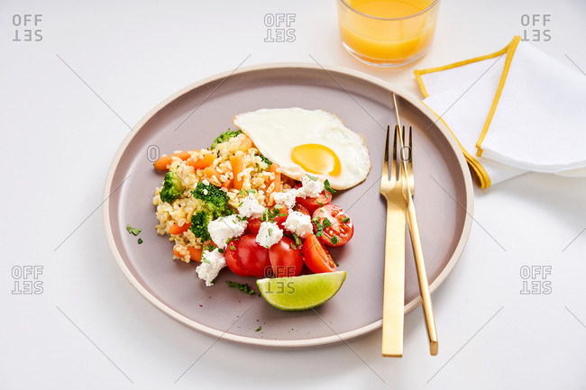 Healthy dish with spelt, goat cheese, tomatoes and egg