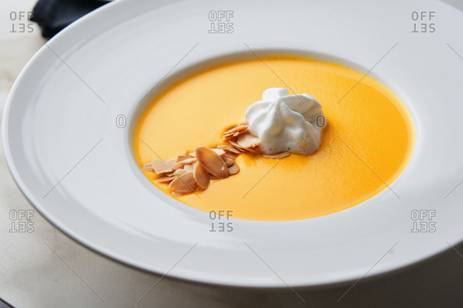 Delicious creamy carrot soup with toasted slivered almonds and coconut foam