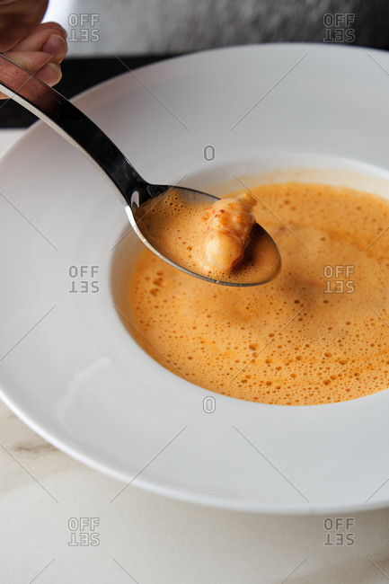 Cropped view of hand holding spoon over a plate of delicious foamed bisque soup with langoustines