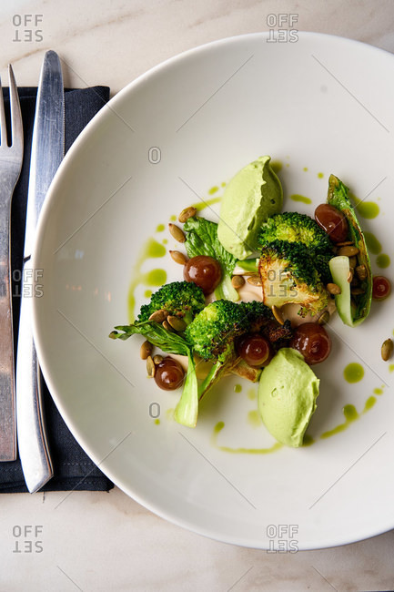 Healthy gourmet dish with bok choy and broccoli on white marble table