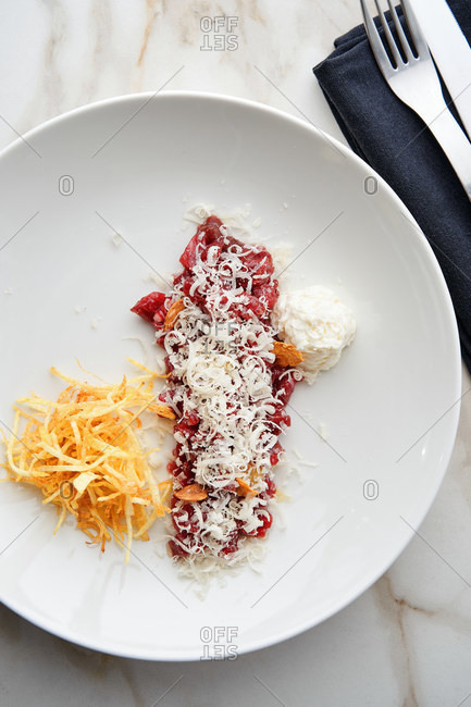 Beef tartar with parmesan mousse on white marble table