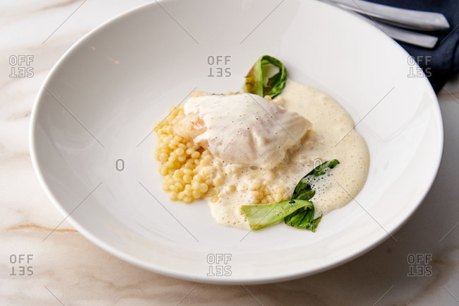 Fusion dish of baked cod with Beurre Blanc sauce, Israeli couscous and grilled vegetables