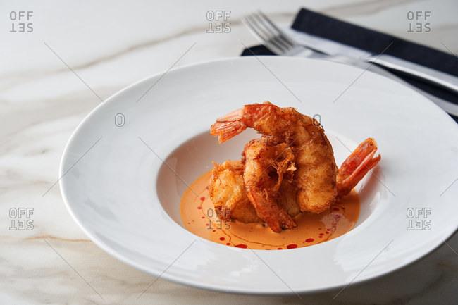 Close up of crispy batter fried shrimp appetizer served on a white plate