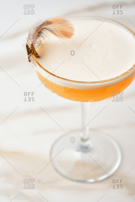 Orange mixed cocktail with foam garnished with a feather on a marble table