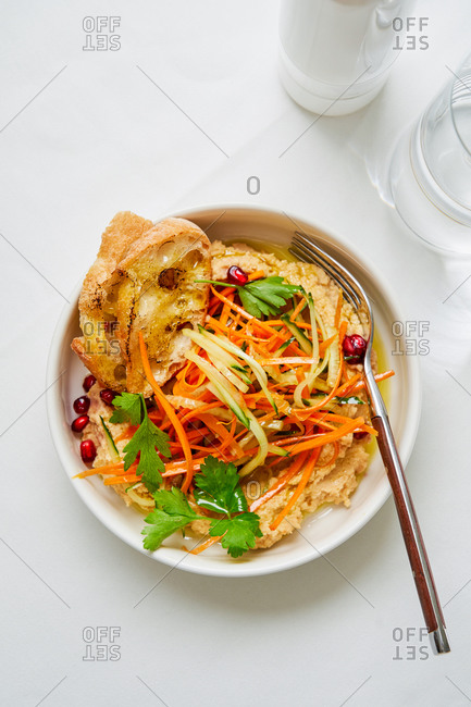 Lebanese chickpea and tahini dip with vegetable salad and baguette on white background