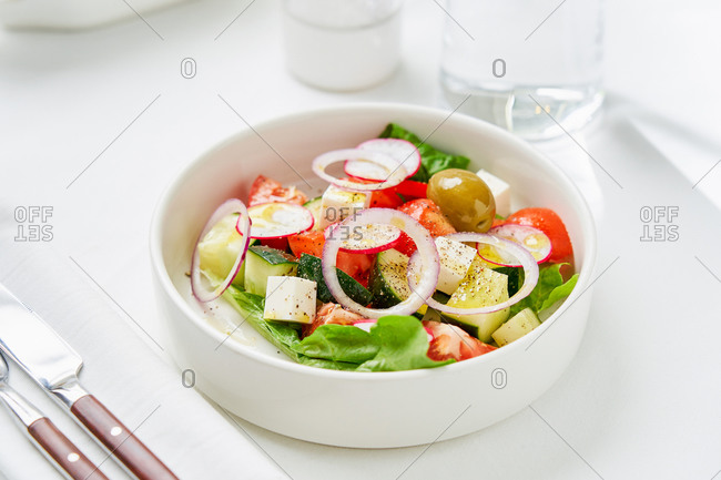 Simple Greek salad loaded with lots of fresh veggies, olives and feta on light background