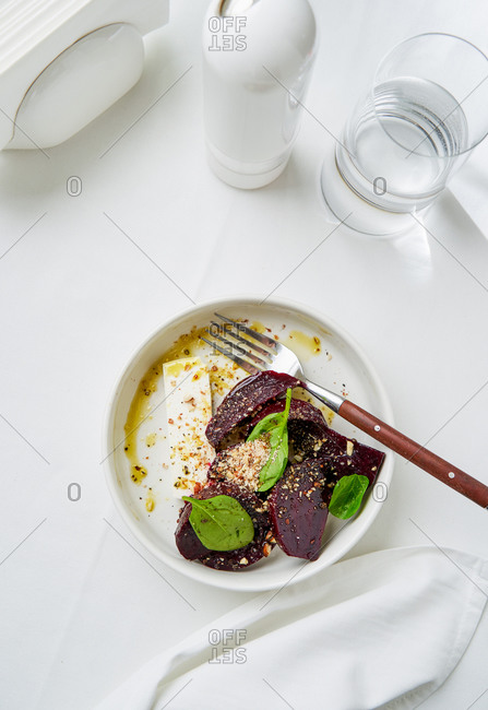 Salad with beetroot, goat cheese and baby spinach on white background