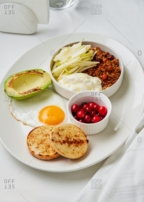 Healthy and balanced breakfast dish with granola, yogurt, apple, cranberries fried egg and grilled avocado