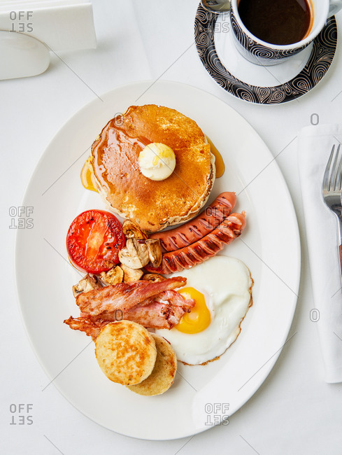 American style Breakfast dish with pancakes, sausages, tomatoes, bacon and sunny side up