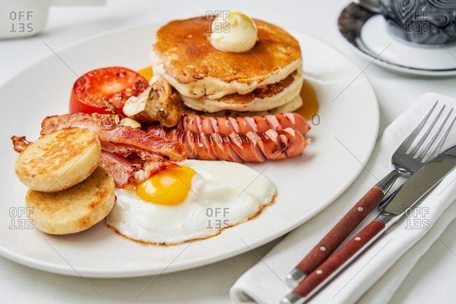 Full English breakfast with pancakes, sausages, tomatoes, mushrooms, bacon and a fried egg