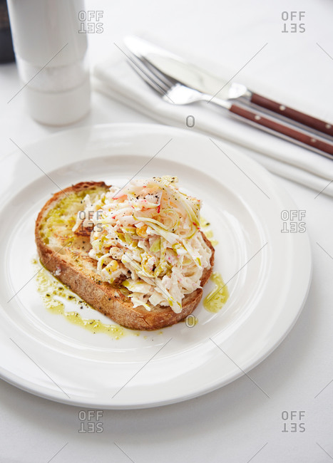 Crab salad toast with homemade mayonnaise served on white plate in a restaurant setting