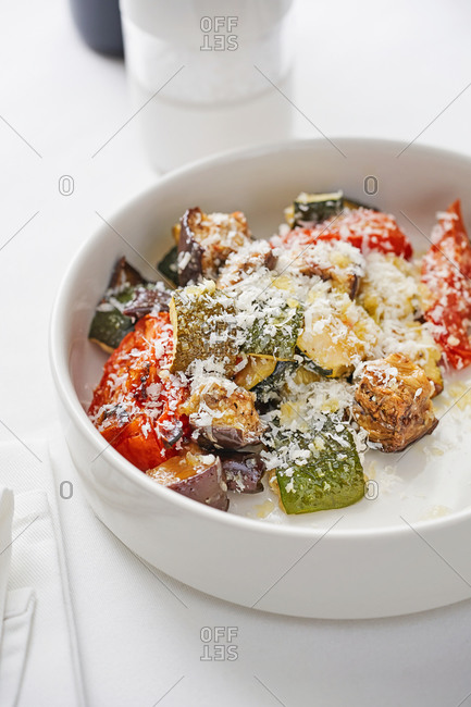 Warm salad of grilled vegetables with parmesan cheese served in a bowl on white table