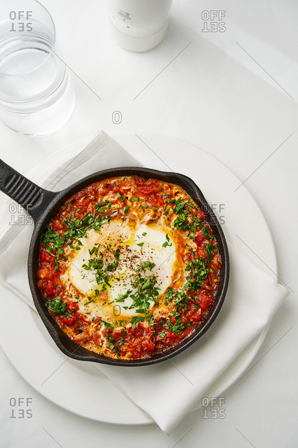Hot cast iron pan with traditional Israeli breakfast shakshuka with cheese and eggs