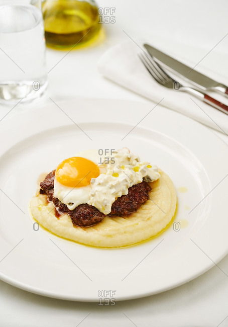 Beefsteak with fried egg over potato mash