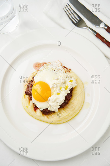 Beautiful brunch dish of beef steak, sunny side up and creamy mashed potatoes on white table