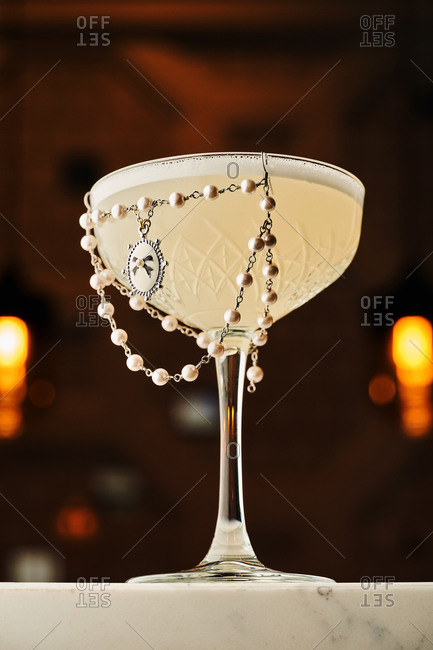 Beautifully decorated cocktail in tall glass on marble table