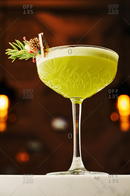 Bright and festive green cocktail decorated with a pine brunch and cone