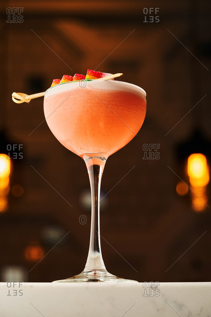 Strawberry pink cocktail served on white marble bar countertop