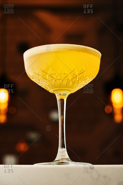 Stylish yellow cocktail on white marble bar countertop