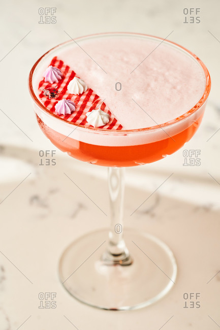 Elegant pink cocktail with foam and edible meringue decoration served on light marble background