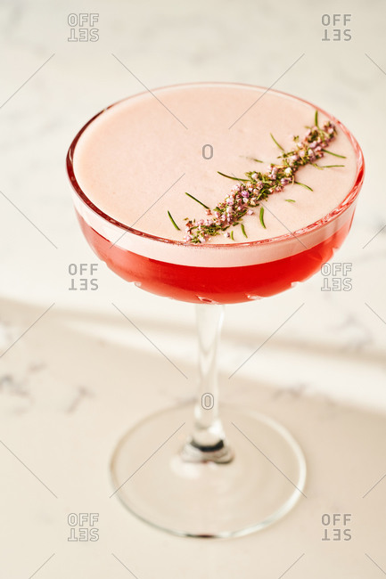 Beautifully garnished pink lady cocktail on white marble bar countertop