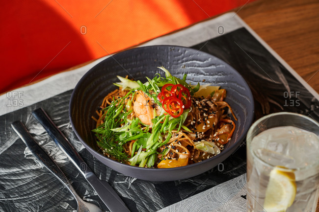 Colorful Asian style dish of stir fried noodles with shrimps and vegetables