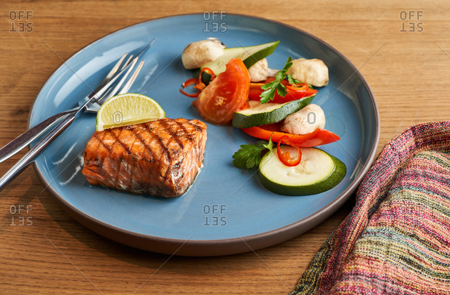 Balanced lunch of grilled salmon steak and  vegetable salad