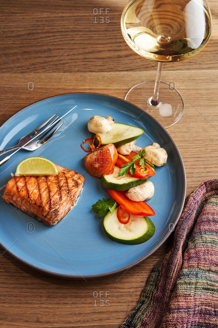 Salmon steak served with grilled vegetables and a glass of white wine
